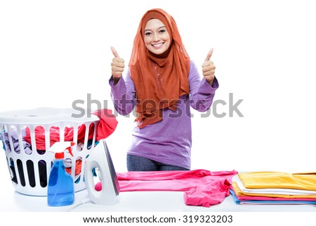 portrait of young woman wearing hijab ironing clothes and giving two thumbs up isolated on white - stock photo