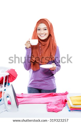 portrait of young woman wearing hijab ironing clothes while enjoying a cup of coffee isolated on white - stock photo