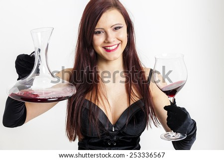 portrait of young woman with a glass of red wine and carafe - stock photo