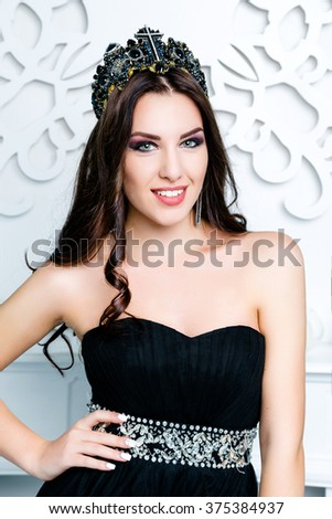 Portrait of young woman with black cross earring and crown, bright make up. Perfect Creative Make up and Hair Style. - stock photo