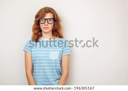 Portrait of Young woman with black glasses standing against wall. - stock photo