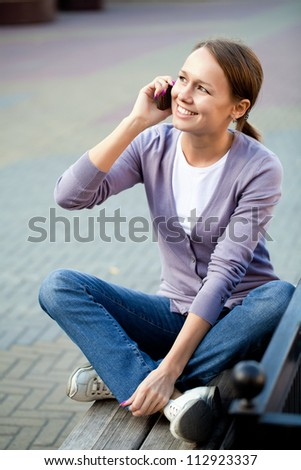 Portrait of young woman with cell phone outdoor - stock photo