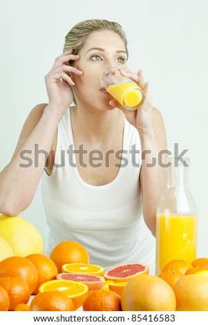 portrait of young woman with citrus fruit and orange juice - stock photo