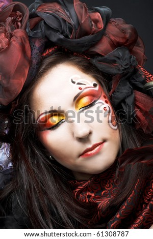 Portrait of young woman with creative make-up in black and red colors - stock photo