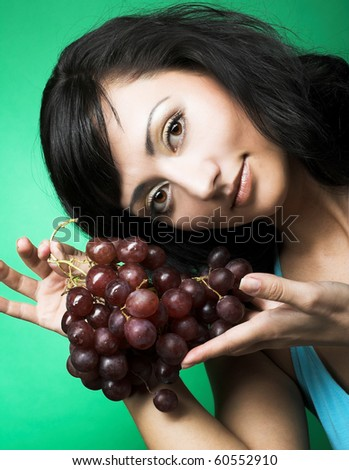 Portrait of young woman with dark grape - stock photo