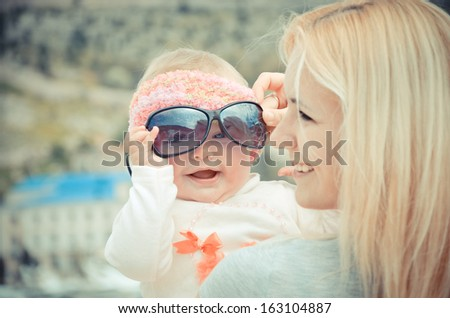 Portrait of young woman with daughter outdoors - stock photo