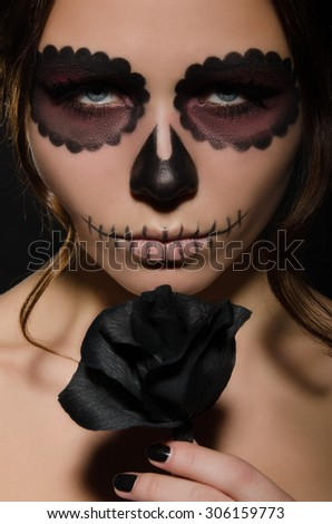 portrait of young woman with face art and flower studio shot - stock photo