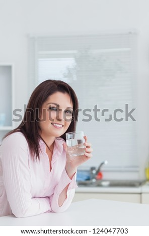 Portrait of young woman with glass of water in the kitchen - stock photo