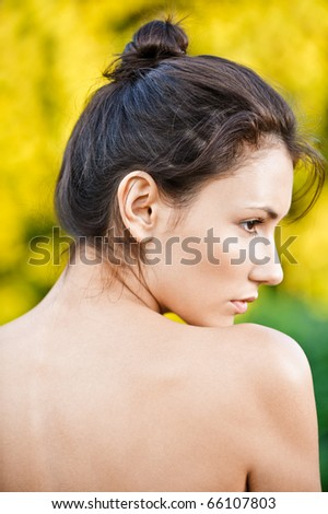 Portrait of young woman with naked shoulders in profile, against autumn nature. - stock photo