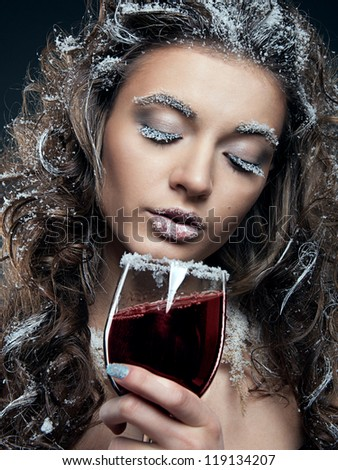 Portrait of young woman with snow make-up with a glass of wine. Christmas snow queen - stock photo
