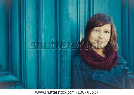 Portrait of young woman with wool vinous snood-scarf outdoors, looking at camera - stock photo