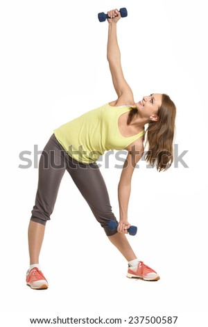 Portrait of young woman workout with dumbbells on white - stock photo