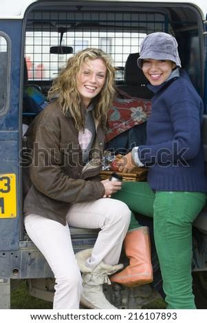 Portrait of young women in front of van - stock photo