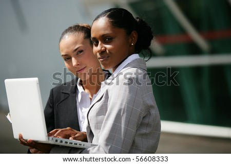 Portrait of young women in suit in front of a laptop computer - stock photo