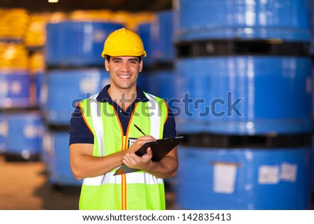 portrait of young worker in warehouse recording stock - stock photo