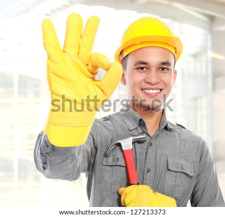 Portrait of young worker with tool belt giving you thumbs up - stock photo
