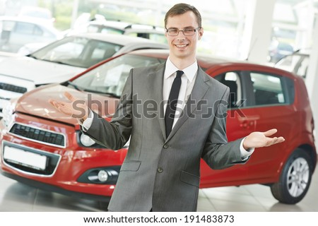 Portrait og salesperson or manager of car automobile dealer welcoming with open arms - stock photo