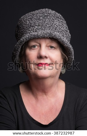 Portrait older woman against a black background - smile - stock photo