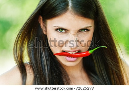 portrait on green background dark-haired sexy girl seductively baring tanned shoulders with red chili peppers in his tooth - stock photo