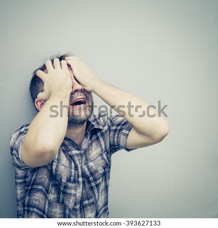 portrait one sad man standing near a wall and covers his face at the day - stock photo