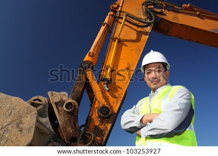 portrait operator of excavator standing on location site - stock photo
