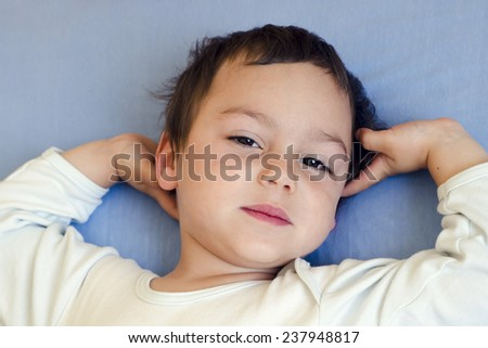 Portrait os a sleepy or waking child lying in a bed, top view. - stock photo