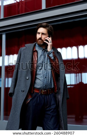 Portrait os stylish fashionable man in elegant coat having phone conversation walking in beautiful hotel hall - stock photo