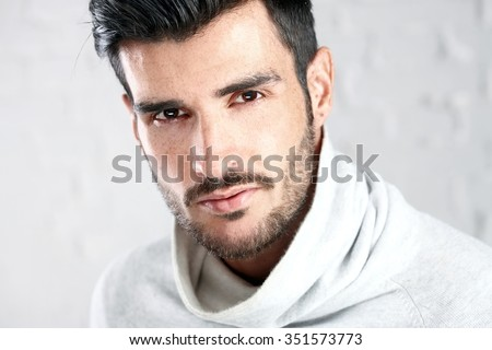 Portrait photo of cool handsome young man looking at camera, white background. - stock photo