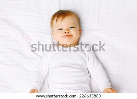 Portrait positive baby lying on the bed, top view - stock photo