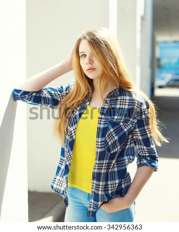 Portrait pretty blonde young girl wearing a checkered shirt in city - stock photo