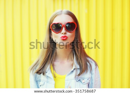 Portrait pretty young woman in red sunglasses blowing lips kiss over colorful yellow background - stock photo