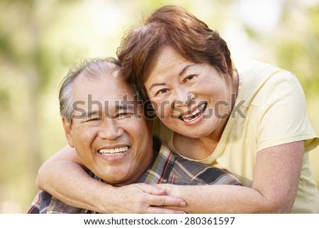 Portrait romantic senior Asian couple outdoors - stock photo