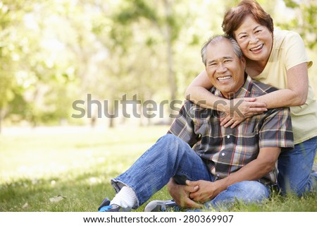 Portrait senior Asian couple in park - stock photo