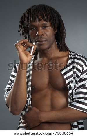 Portrait serious men afro-american with cigarette on gray background - stock photo
