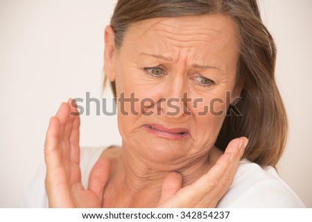 Portrait shocked attractive mature woman looking in disgust, stressed facial expression, isolated, bright background. - stock photo