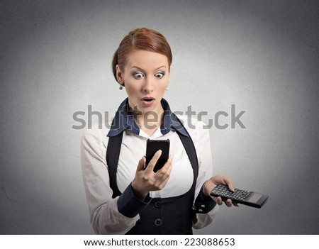 Portrait shocked businesswoman looking on smart phone holding calculator unexpected financial bills charges isolated grey wall background. Human face expression, emotion, body language, reaction - stock photo