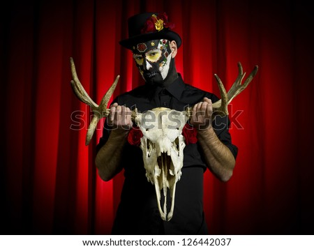 Portrait shot of a scary male with sugar skull paint posing with animal skeleton in hand over red background. - stock photo