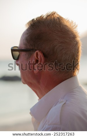 portrait shot of an old man on the beach looking at the sunset - stock photo