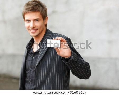 Portrait shot of smiling young businessman showing blank business card. Focus on card. Outdoor. - stock photo
