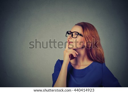 Portrait side profile happy beautiful woman thinking looking up isolated on grey wall background with copy space. Positive human face expressions, emotions, feelings, body language, perception - stock photo