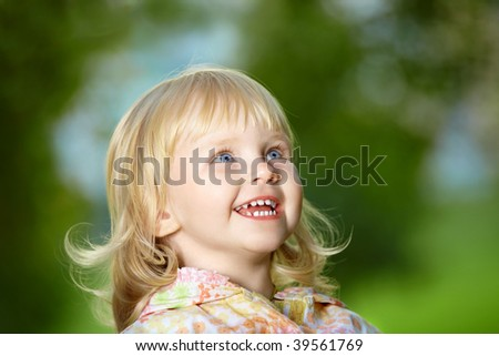 Portrait - small amusing blonde girl laughs in park - stock photo