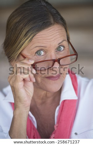 Portrait smart attractive mature business woman with glasses and curious expression, blurred background. - stock photo