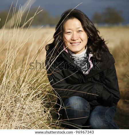 Portrait smiling asian woman looking at camera in the field - stock photo