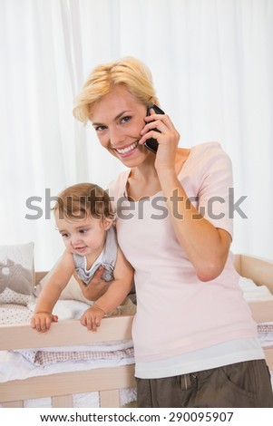 Portrait smiling blondewoman with his son phoning at home in bedroom - stock photo