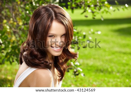 Portrait smiling curly woman in a summer garden - stock photo