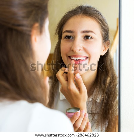 Portrait smiling girl looks in the mirror and uses lip balm - stock photo