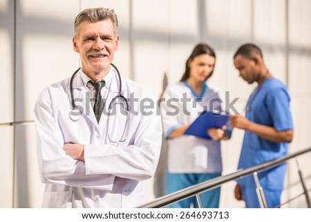 Portrait smiling mature male doctor standing with arms crossed. The background doctors speaking. - stock photo