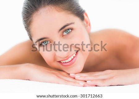 Portrait smiling pretty brunette on massage table with white backgroung - stock photo