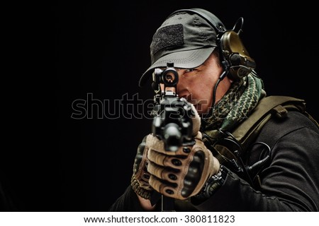 Portrait  soldier or private military contractor holding sniper rifle. war, army, weapon, technology and people concept. Image on a black background. - stock photo