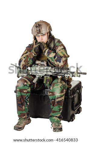Portrait soldier or private military contractor holding with a machine gun and sitting on plastic black case. war, army, weapon, technology and people concept. Image on a white background. - stock photo